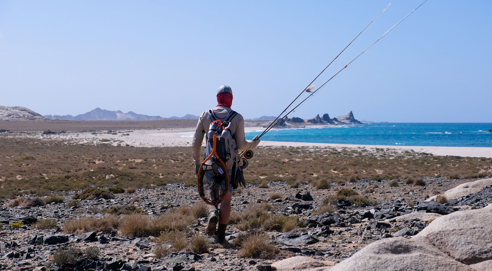 Peter Coetzee hiking across Socotra rods in hand